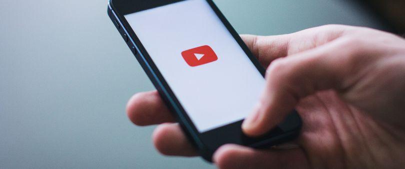 Main tenant un téléphone avec l'application YouTube qui s'ouvre